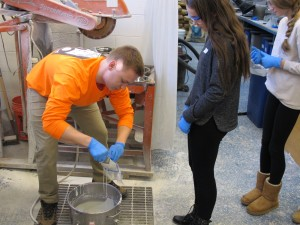 Grad student Dominic Kruszewski pours concrete into a bag for a Glastonbury middle school student.