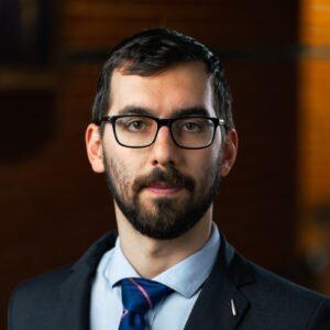 Portrait of Diego Cerrai, wearing a dark suit, light blue collared shirt and a dark blue tie.