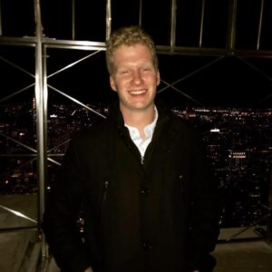 Rising senior Ethan Cummiskey is pictured in front of a nighttime cityscape.