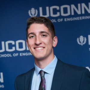 Rising senior Steven Porter stands in a suit jacket and tie in front of a blue background on which the UConn wordmark printed.