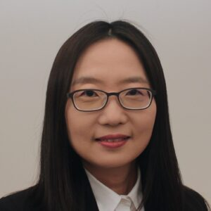 Portrait of Dr. Shinae Jang a woman with dark straight hair wearing a black suit jacket and a white collared shirt.
